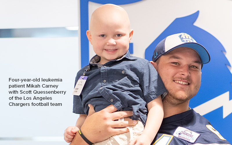 Four-year-old ALL patient Mikah Carney with Scott Quessenberry of the Los Angeles Chargers football team